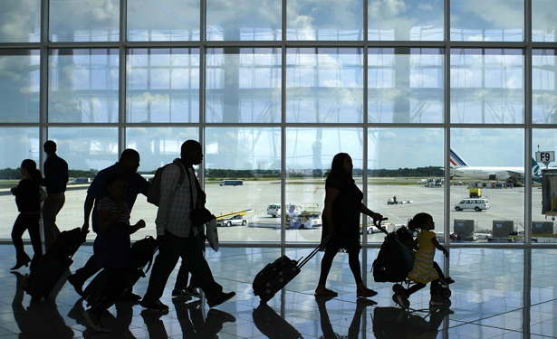 Passengers walk through airport.